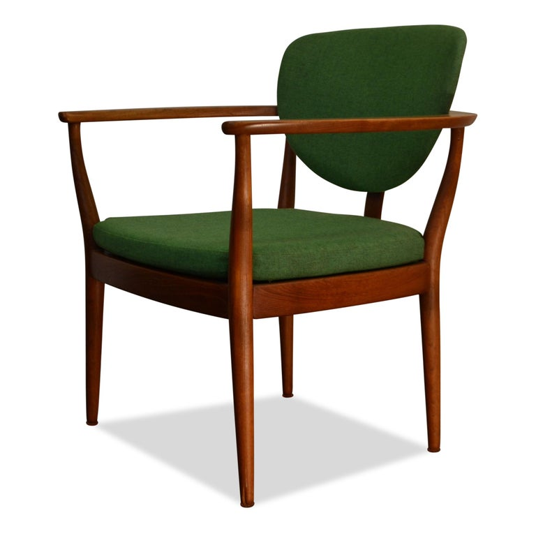 Super stylish vintage lounge chair designed by an unknown Danish designer. Made out of beautiful teakwood, upholstered in beautiful green woven fabric, loose seat cushions and featuring gorgeous curved backrest. This chair just breaths 1960s Danish