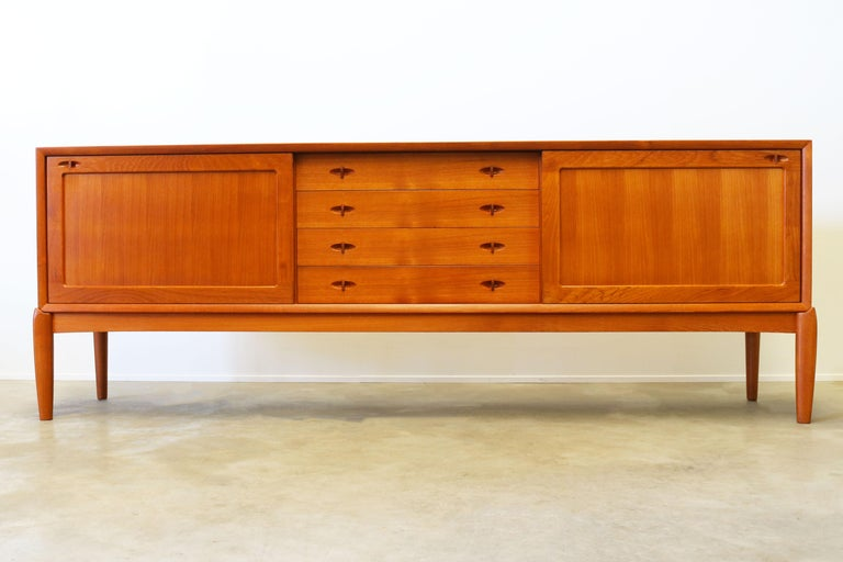 Magnificent Danish design sideboard designed by H.W. Klein for Bramin in the 1950s. The sideboard is made from solid teak wood and is famous for its combination between straight and organic lines with in particular the organic (solid wood) sculpted