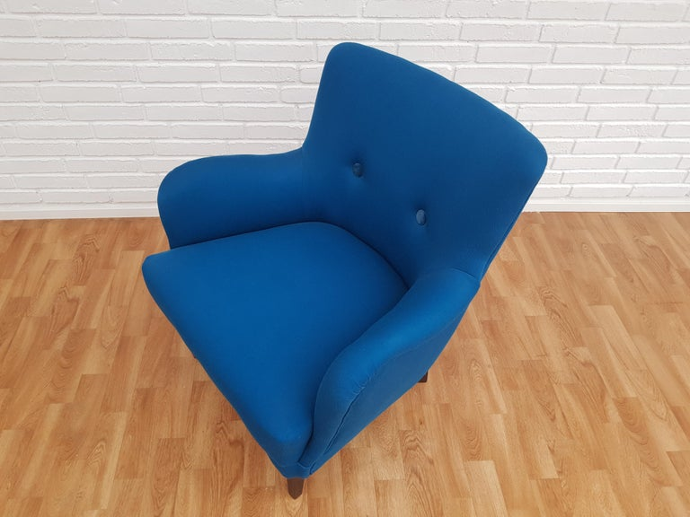 Danish armchair. New reupholstered in quality turquoise blue wool fabric by professional furniture upholsterer at Retro Møbler Galleri. Velour buttons. Made by Danish furniture manufacturer circa 1970. The seat with original