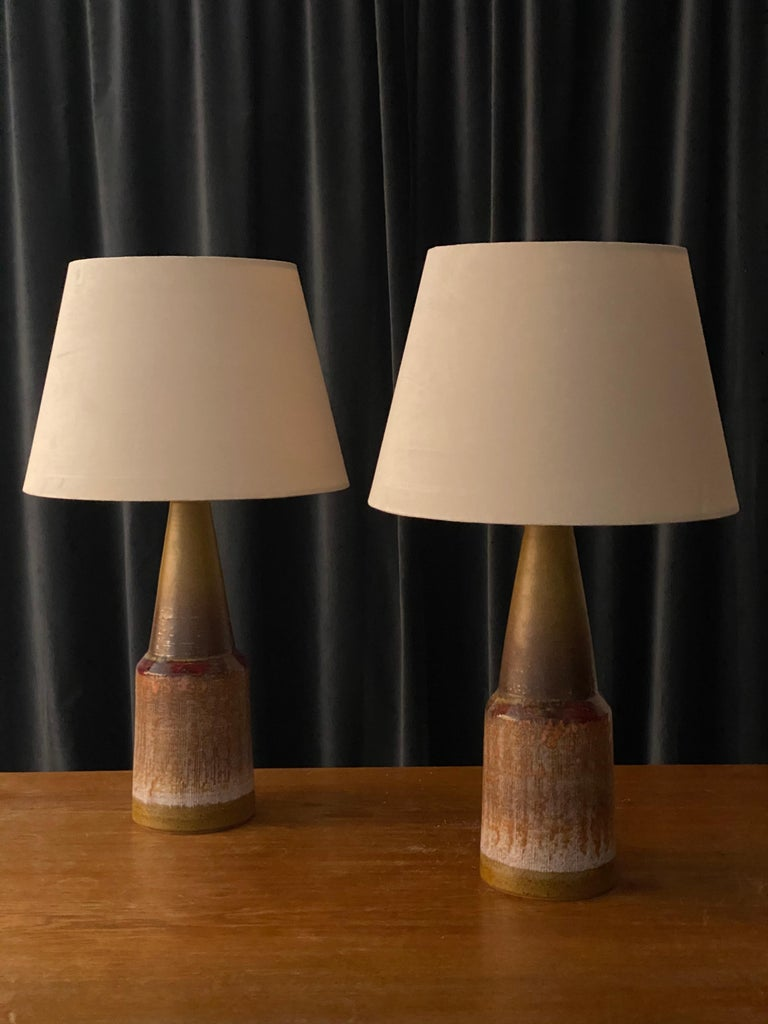 A pair of highly sculptural and sizable stoneware lamps. Features a highly artistic beige / brown / grey / red glaze. Marked