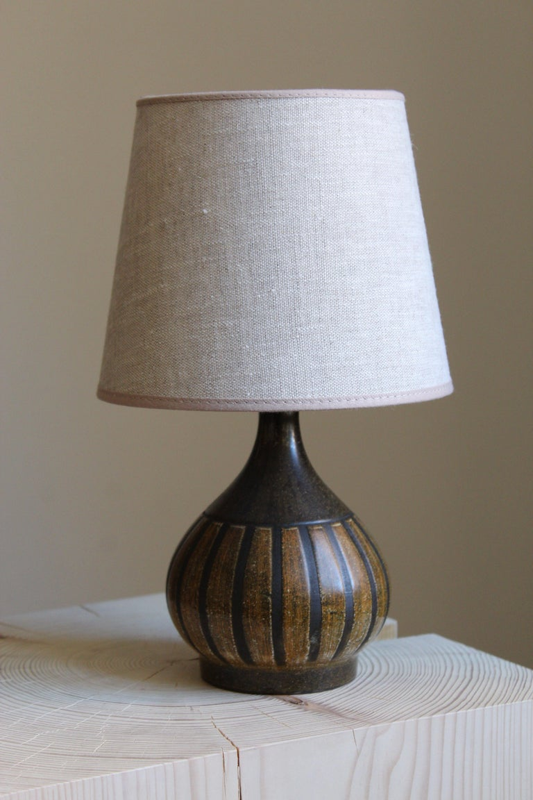 A small table lamp. Signed. Designed and produced in Denmark, 1960s. Unidentified designer and maker. Brand new high-end linen lampshade.