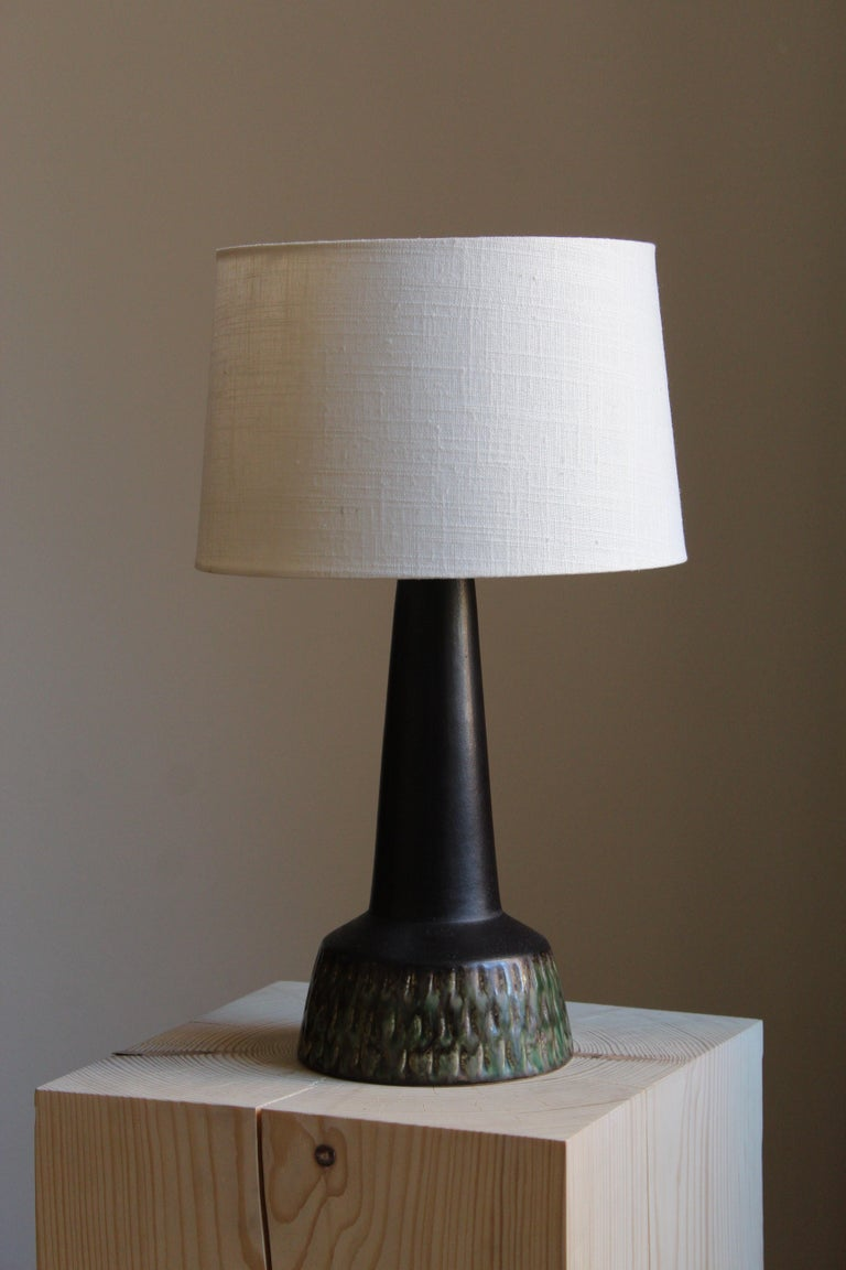 A modernist table lamp. Designed and produced in Denmark, 1960s. Unsigned.   Brand new high-end linen lampshade is included  Other designers of the period include Axel Salto, Arne Bang, Carl-Harry Stålhane, Gunnar Nylund and Wilhelm Kåge.