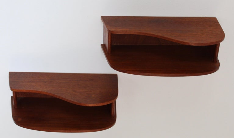 A pair of organic wall-mounted bedside cabinets / nightstands. In solid teak.  Other designers of the period include Finn Juhl, Hans Wegner, Franco Albini, Vladimir Kagan, and Gio Ponti.