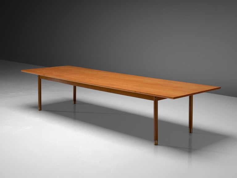 Danish dining or conference table, teak, brass, Denmark, 1950s  A rectangular top is lifted up by four circular legs with brass feet. The large top reaches over the legs. The natural grain of the teak structures the top visually.  VAT within the