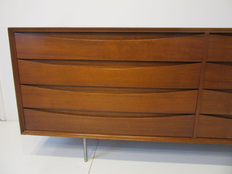 An eight-drawer Arne Vodder dresser chest with the designers signature design cats eye drawer fronts that serve as pulls. The top drawer having divided storage areas and a sliding tray crafted in teak wood and custom delivered with brushed stainless