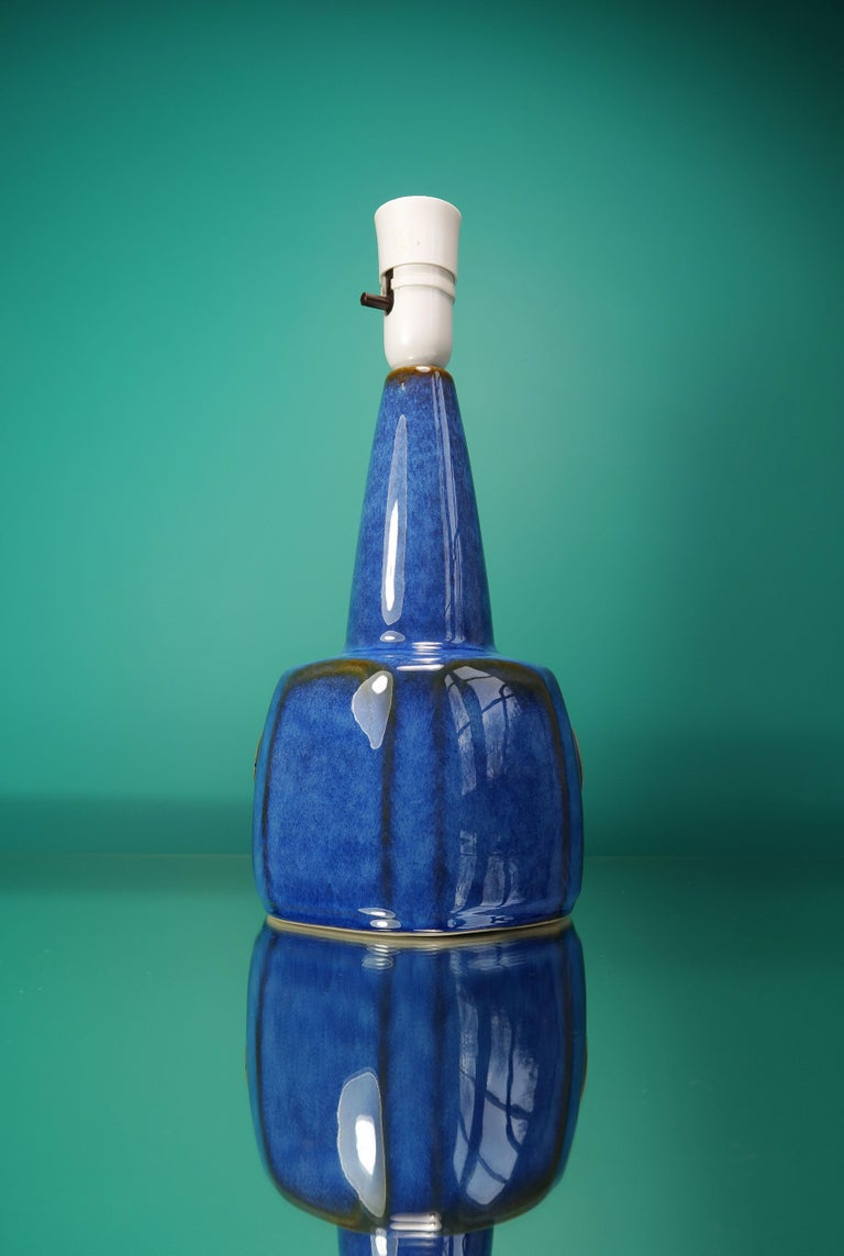 Classic Danish Mid-Century Modern table lamp by designer Einar Johansen. Manufactured by Søholm Stentøj on the island of Bornholm in the 1960s. Smooth and shiny cobalt and azure blue runny glaze over caramel glaze. Graphic circular symbol on belly.