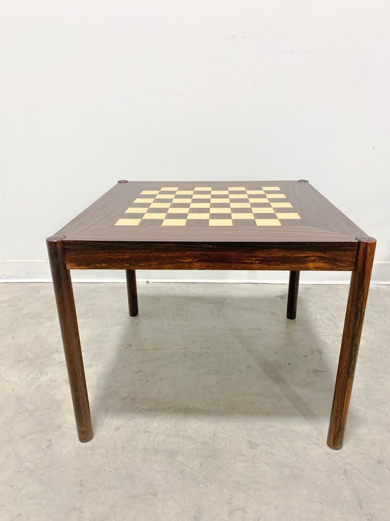 Eye-catching flip top chess table designed by George Petersen and made in Denmark. Solid rosewood legs with veneered top and sides. Chessboard on one side of top and rosewood grain on other. Legs bolt on making it easily collapsible for shipping or