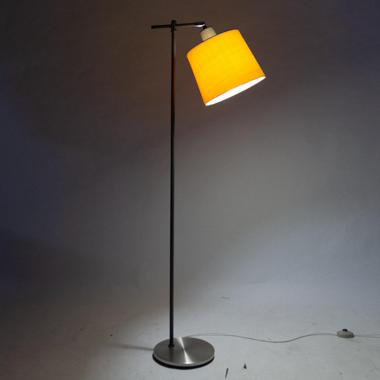 Danish floor lamp by Jo Hammerborg for Fog & Mørup, 1960s. Tall midcentury floor lamp with adjustable head. Round base in brushed metal. Vertical rod in grey with chrome and black fittings. Original shade in woven fabric. Style is Scandinavian