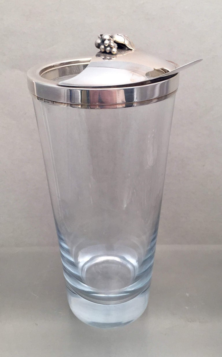 A beautiful cocktail shaker bar set made of crystal with a slight blue hue and sterling silver handles and lids from the mid-20th century. Set comprises of:  - a cocktail shaker 9 3/4 inches tall and 4 inches in diameter at top, with an enamoring
