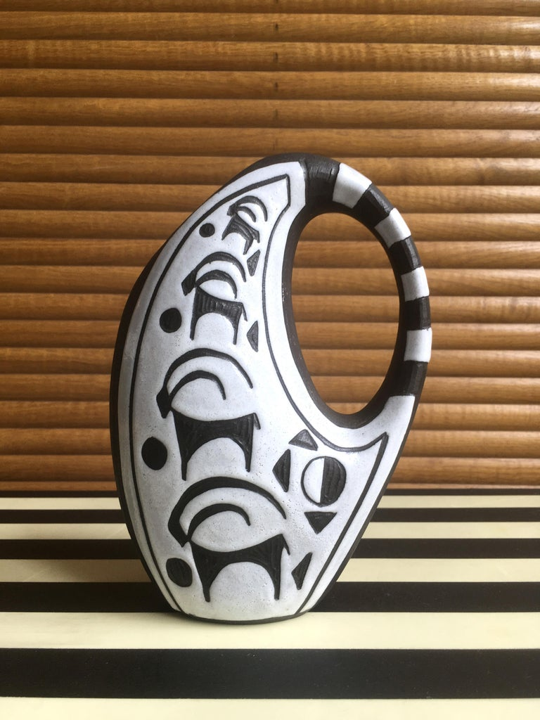 Beautiful handmade Danish modernist ceramic pitcher vase from the Tribal series by ceramic artist Marianne Starck (1931-2007). Smooth rounded shapes with striped handle. White glaze with hand-carved stylized animal decor on raw anthracite clay. Made