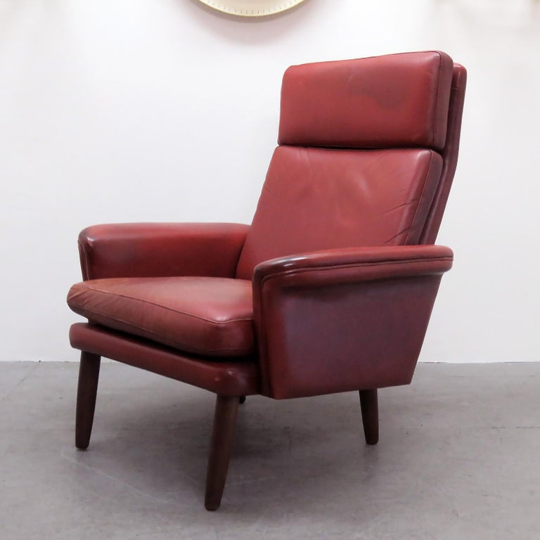 Great Danish high back leather lounge chair in well-aged red leather with loose down cushions and teak legs.
