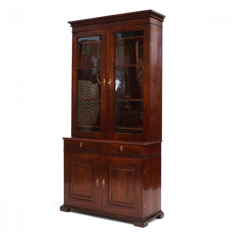 Late Empire vitrine or bookcase cabinet. Made of radial cut mahogany with beautiful grain. In two parts. The upper cabinet with a pair of paned glass doors and adjustable shelving inside. Lower section with two drawers above a pair of doors with