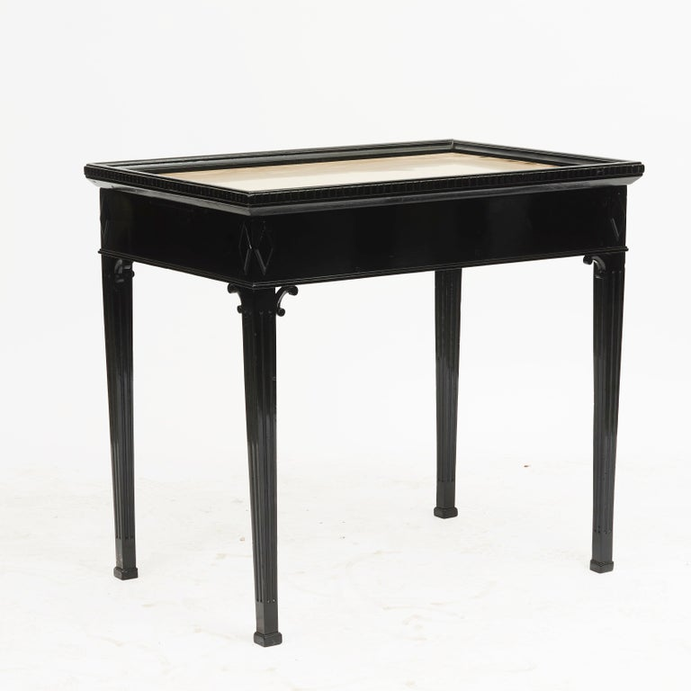Tray table with brass top. Fluted edge, apron with motif in the form of rhombuses above fluted legs with block feet. Sides with twin pull-out candle slides. Louis XVI style, Denmark, mid-19th century.