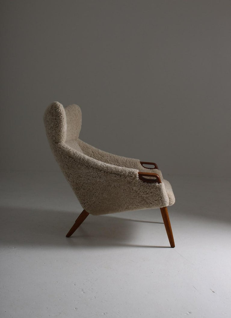 Danish high back wing chair model 55 by Kurt Østervig for Rolschau Møbler, Vejen. This majestic chair looks great from any angle and, on top of that, is as comfortable as it looks. The details in teak match the off-white sheep skin