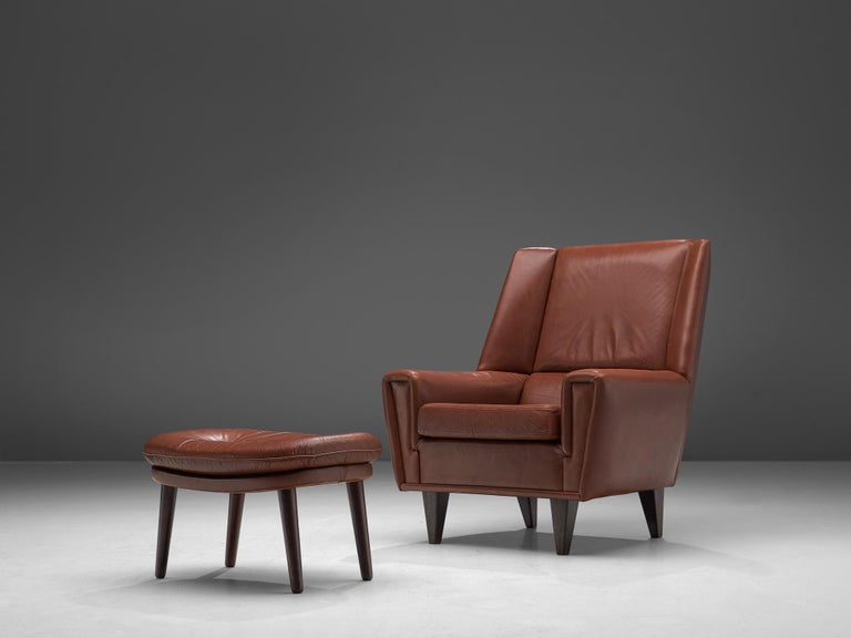 Danish cabinetmaker, lounge chair with ottoman, in brown leather and oak, Denmark, circa 1960.  This chair with ottoman is made to reach an ultimate level of comfort as can clearly be recognized in the design. This Danish chair features