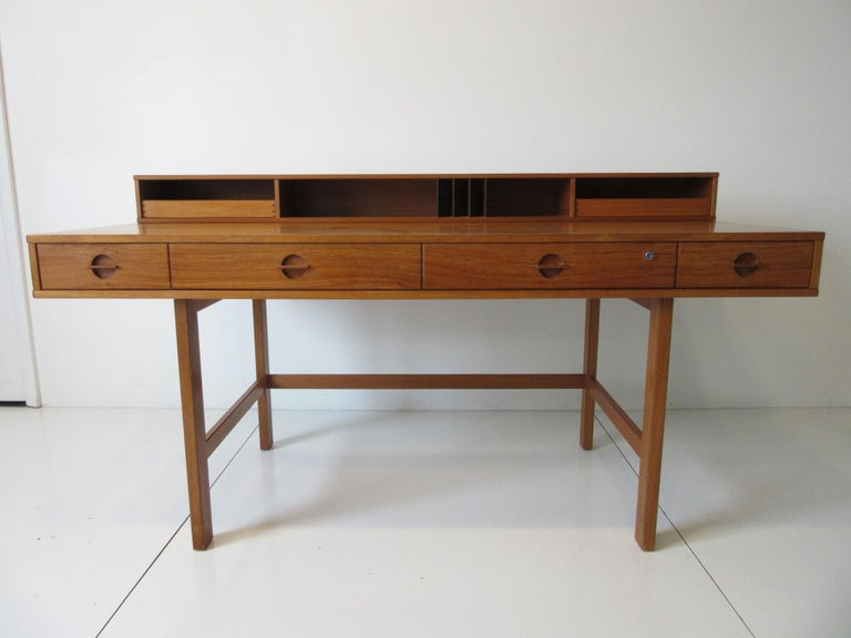 A wonderful well designed and Classic teak flip top desk with four front drawers having built in matching pulls, two upper slide out storage drawers, letter compartment and bins. The back side has three open storage bins and when the back side is