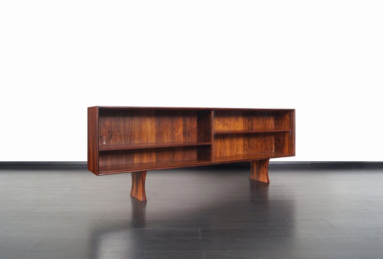 Danish modern Brazilian rosewood bookcase or credenza designed by Bernhard Pederson & Son. This low profile bookcase features two sliding glass doors that smoothly opens to reveal two adjustable shelves. The case sits on two solid rosewood pedestal