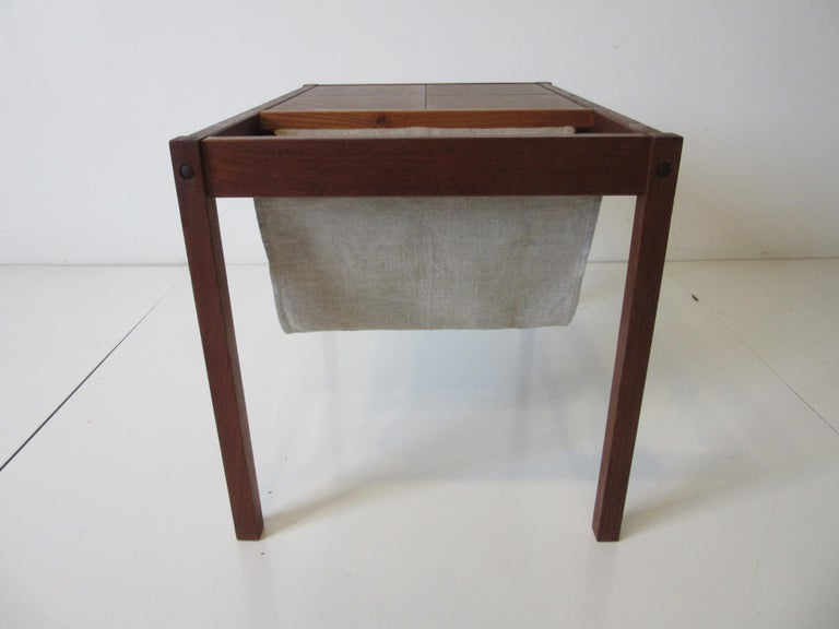 A dark teak wood framed magazine rack with hanging fabric sling the other end of the top having four large glazed pottery tiles. Retains the ink stamp of origin made in Denmark in the manner of BRDRK Furbo.
