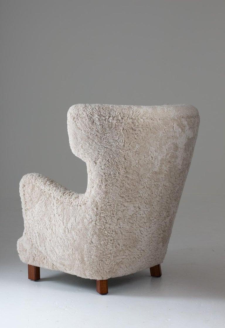 Danish high back wing chair manufactured in Denmark, circa 1940.  This majestic chair looks great from any angle and, on top of that, is as comfortable as it looks. It's been upholstered in off-white sheepskin and cognac leather