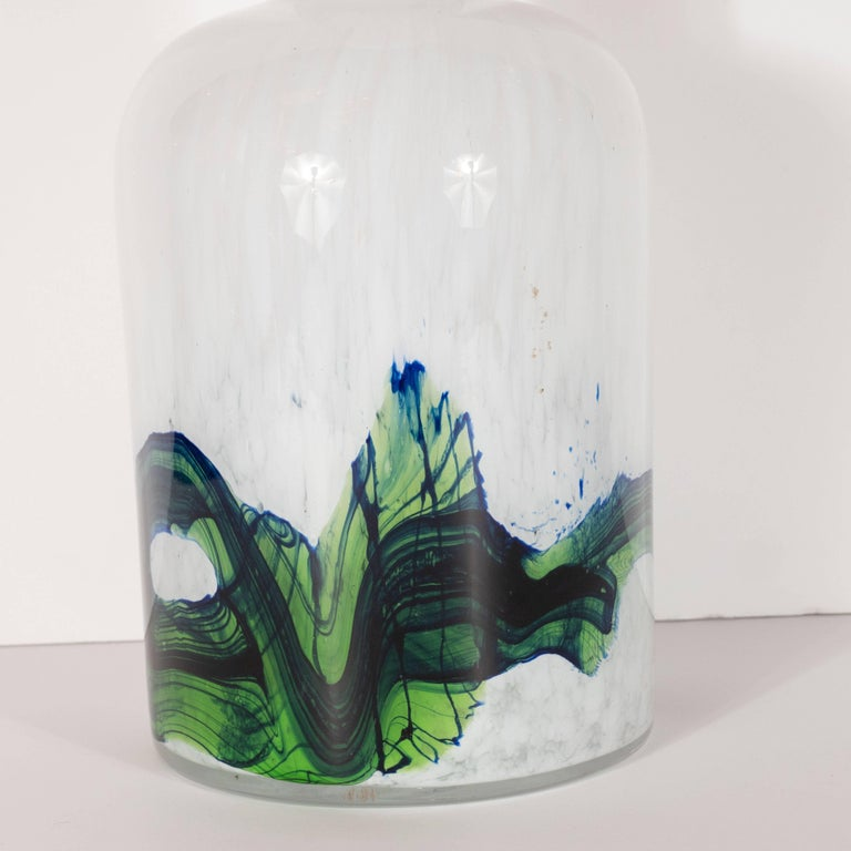 This stunning Scandinavian Mid-Century Modern vase was designed by the esteemed Otto Brauer and handblown by Holmegaard in Denmark, circa 1960. The piece features a cylindrical body with curved shoulders that ascends into a slender cylindrical neck