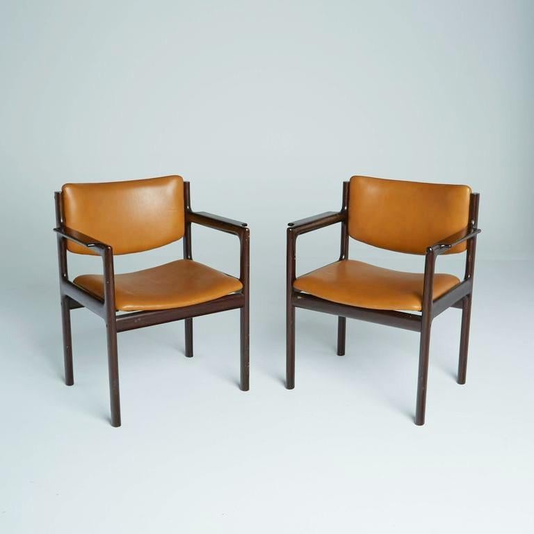 This pair of caramel Mid-Century Modern armchairs are as durable in construction as they are attractive in their Danish modern design. The caramel leatherette upholstery of the seats and backs of each chair is framed by rich, dark rosewood with