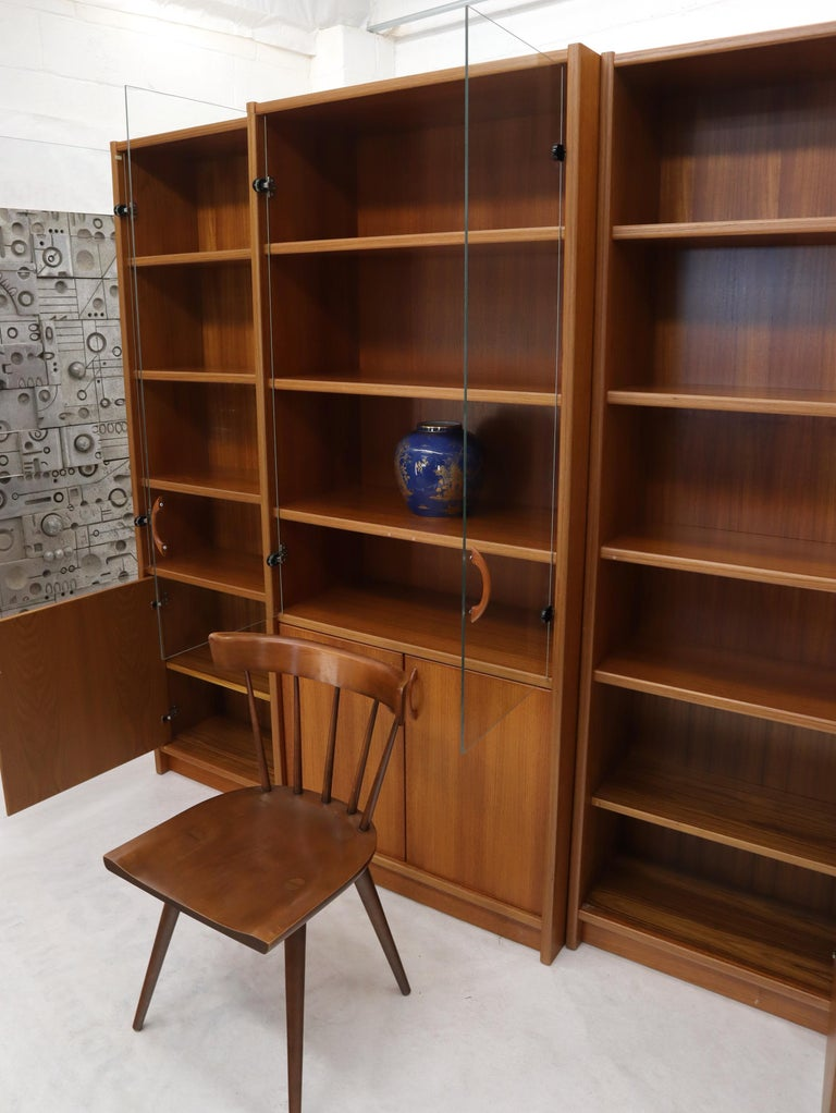 Danish modern teak wall unit vitrine consisting of three individual cabinets with adjustable shelves glass doors compartments.