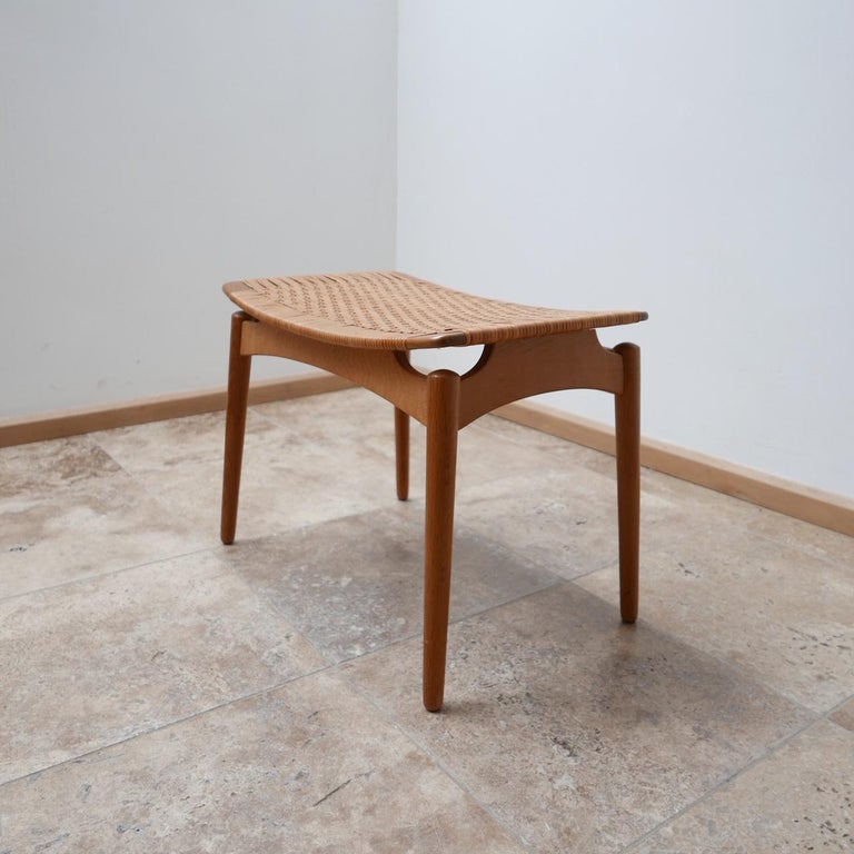 A stylish midcentury stool by Sigred Omann, designed for Ølholm Møbelfabrik.  Denmark, circa 1950s.  Cane top, the base is either oak or a light teak.  Amazing stance and form.  Perfect as an occasional stool or a side table for books and