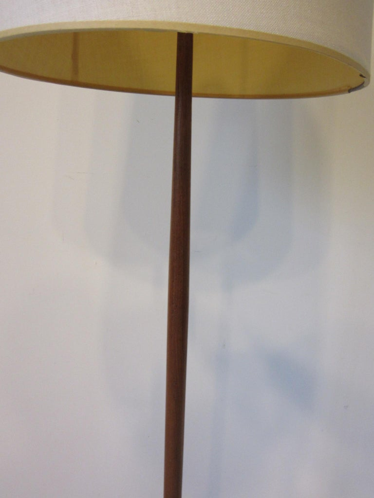 A wonderful Danish floor lamp with tapered shaft having brass detail to the round base which is very well weighted. A light and balanced look for that midcentury interior, made in Denmark.