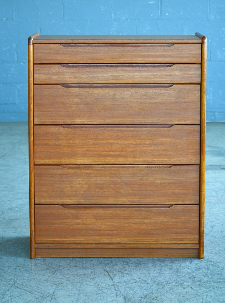 Beautiful Danish 1960s teak tall dresser or chest or drawers. Sharp distinct design lines and very high build quality. Teak veneer with great grain and color and edges of thick solid teak overall very good condition with only very minor age