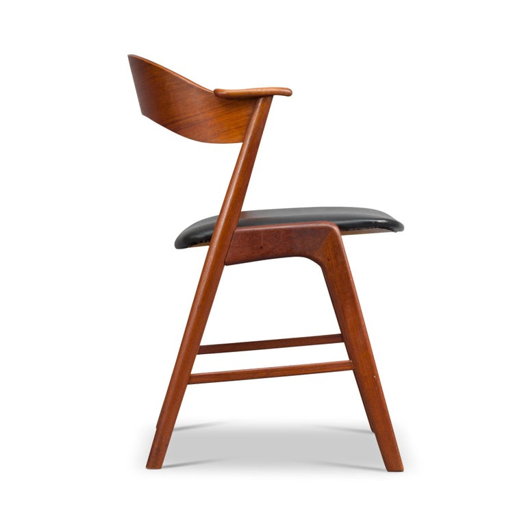 A typical Kai Kristiansen design style on this elegantly cut dining chair. Kristiansen selected his typical backrest and armrest connected to the backlegs construction. We call this chair simply the ply back chair because of the teak 1 cm thick