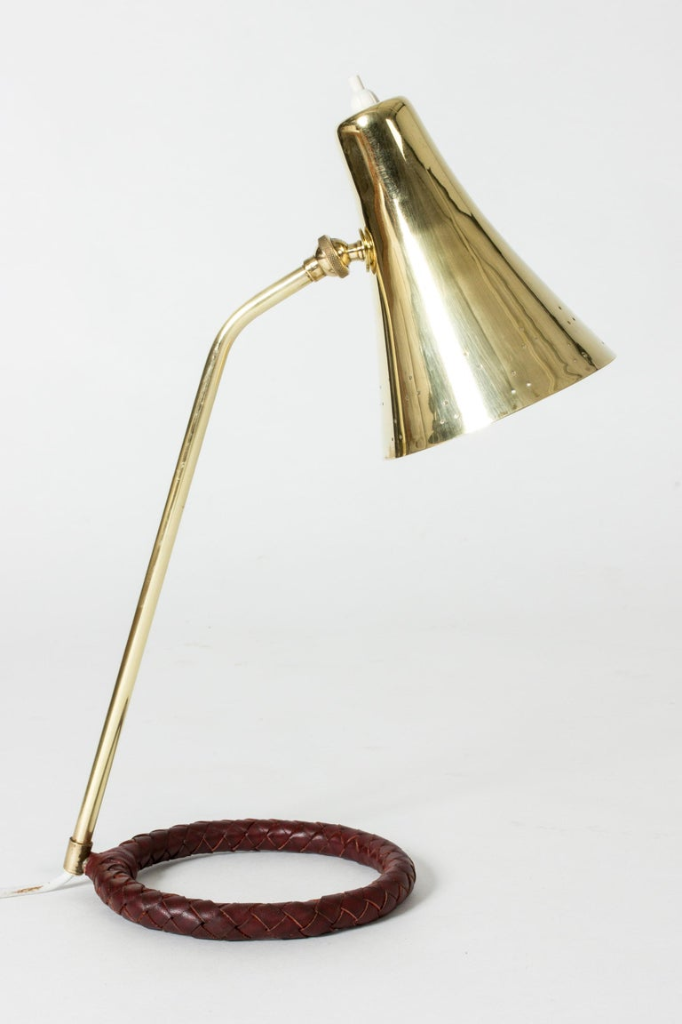 Elegant Danish midcentury brass table or desk lamp with a cool round base. Shade perforated with small decorative holes around the rim, base with wreathed brown leather.
