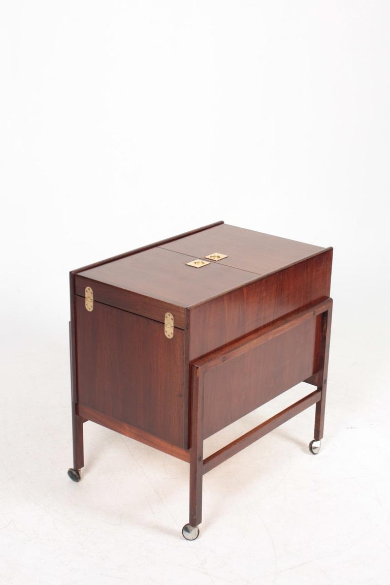 Midcentury modern dry bar in rosewood. It is designed and made Dyrlund in Denmark.