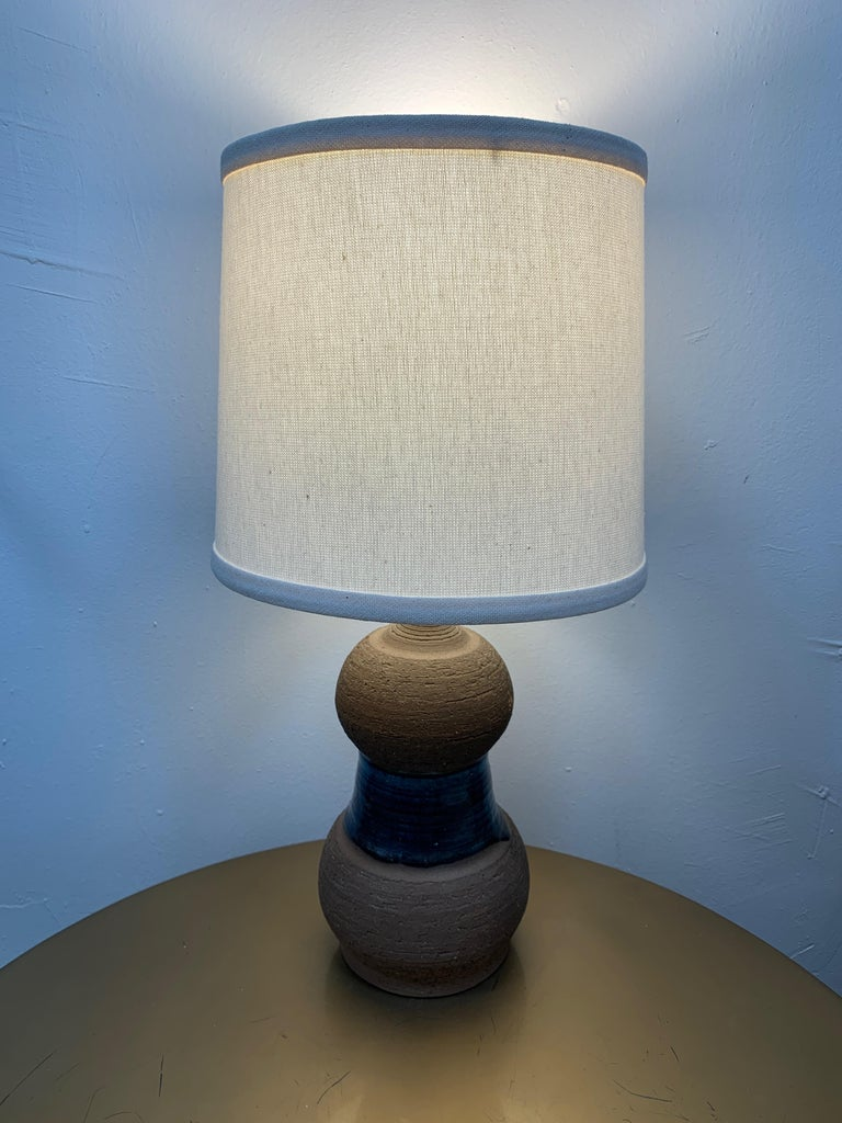 Vintage hourglass shaped lamp made from clay with a band of blue glaze in the center. New lampshade. Signed