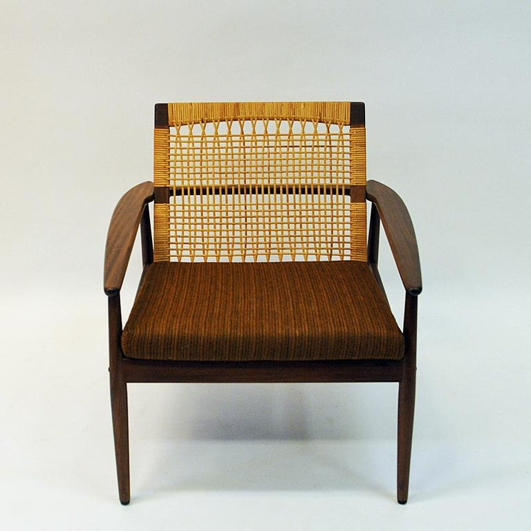 Beautiful lounge chair with woven cane back rest and original dark brown wool cushions by Hans Olsen for Juul Kristensen, Denmark, 1950s. Slightly tilted cane back rest with lovely details on armrests which are gathered into a handle on the back of