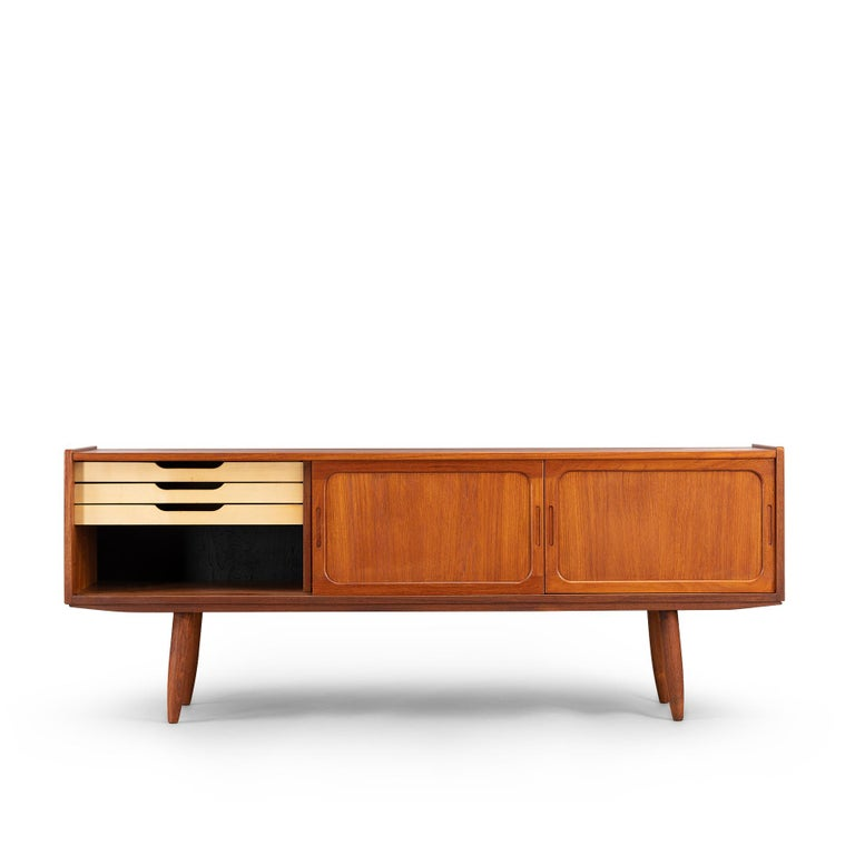 Low sideboard in teak in which you can hide all your pleasures. The color is a beautiful reddish dark brown. The cool grips, framed sliding doors and patterning of the wood make this one a true eyecatcher. On the inside there is all you need with a