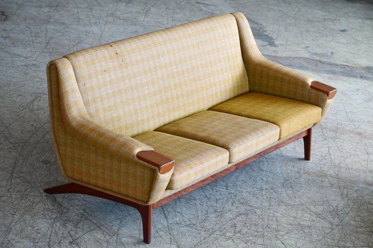 Very elegant and stylish 1960s sofa in the style of Illum Wikkelsø made by Erhardsen and Erlandsen (ERAN) on of the high-end makers of the midcentury era. Raised on a base and legs of solid teak with large teak accents on the armrests. The base and