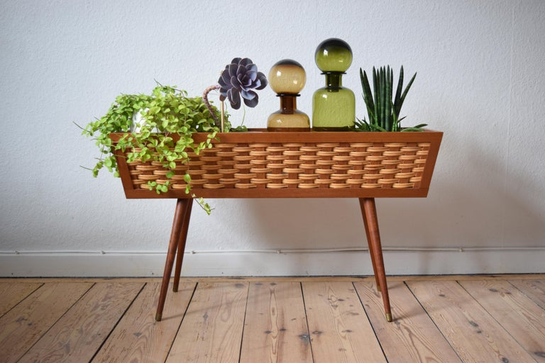 Vintage teak and cane planter manufactured in Denmark in the 1960s. Sits on delicate turned and tapered teak legs with brass 'shoes'. Polystyrene insert. Legs can be removed for easier shipping. Very few marks on this piece.