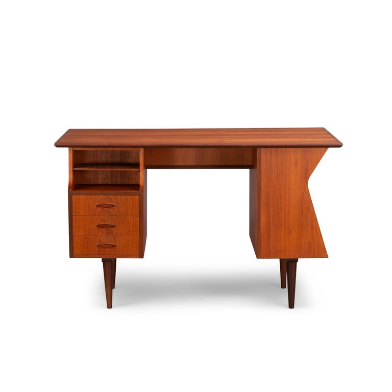 This Danish midcentury rare teak writing desk has been produced during the 1960s. It is made of teak with sculptural shape and handles. The desk features different storage possibilities with a total of five drawers. This bureau can be placed free