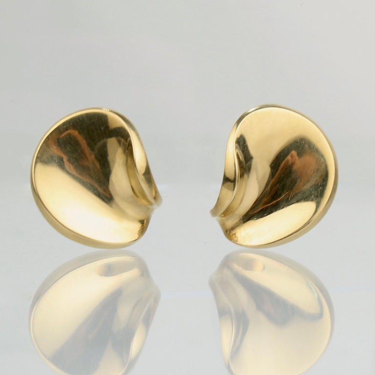 A very fine pair of Georg Jensen 18k gold clip earrings.  Designed by Hans Hansen.  Marked to the reverse: 750 for 18k gold fineness, Georg Jensen, and HaH for Hans Hansen.  Great Danish Modern design!  Length: ca. 27 mm Width: ca. 23 mm  Items