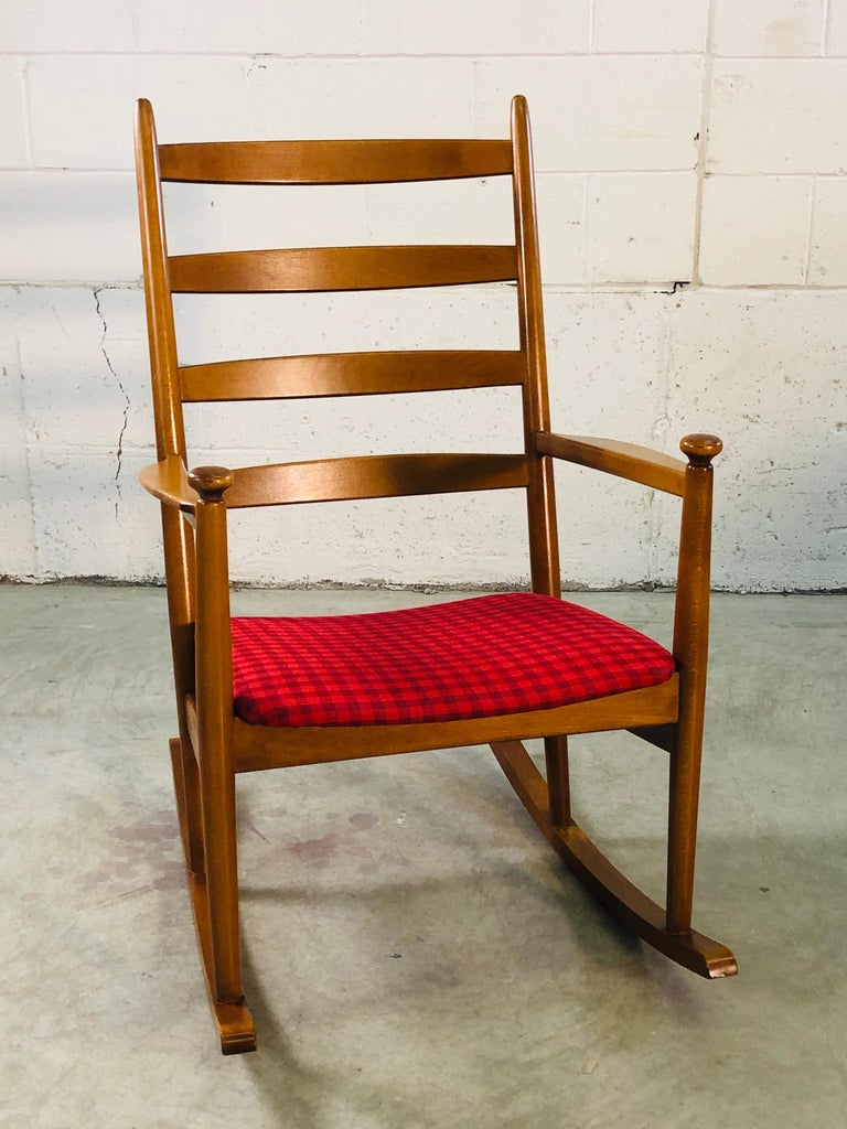 Vintage Danish modern beechwood rocking chair with gigham fabric designed by Niels Eilersen. The rocking chair is very comfortable and well designed with a curved ladder back. No marks.
