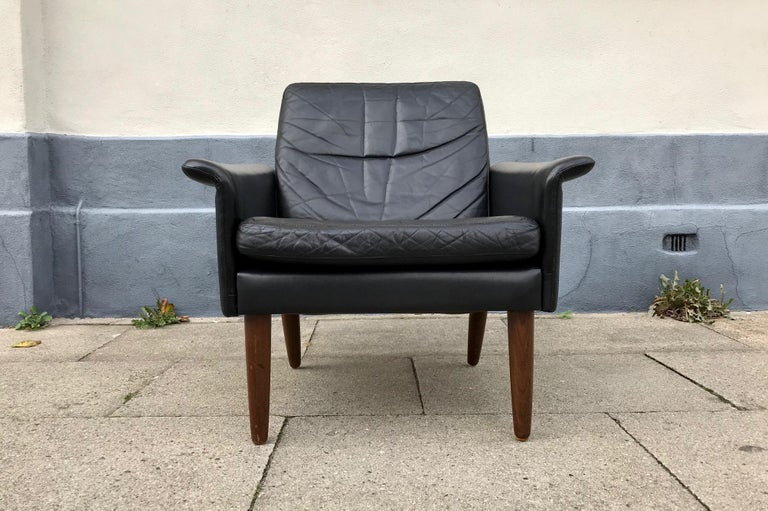 All original Hans Olsen lounge chair designed during the early 1960s and manufactured at CS Moebler in Denmark. This example is upholstered in its original soft black leather and has tapered legs in solid teak.