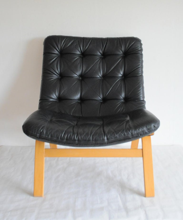 Black leather lounge chair. Leather upholstery in a fine condition. Frame in laminated beech. 