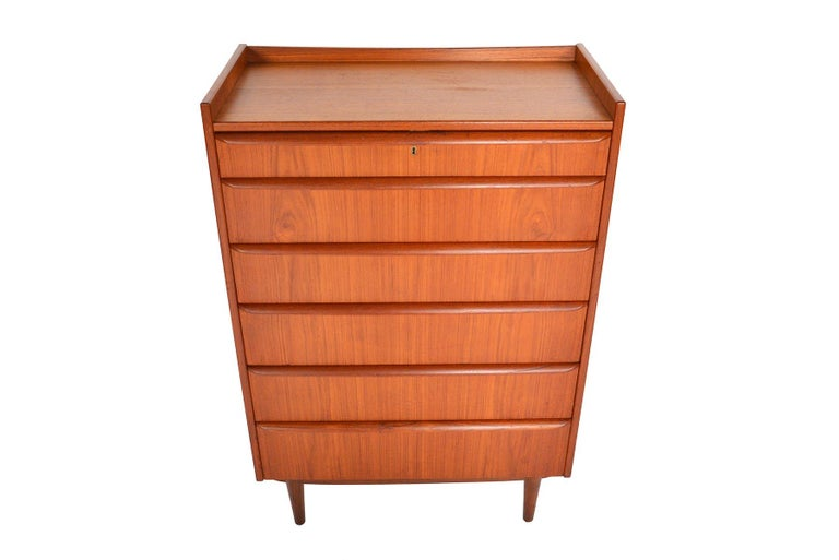 This gorgeous Danish modern six-drawer midcentury teak highboy dresser offers a stunning profile. Drawers become progressively deeper towards the base. Banded in beautifully contrasting afrormosia, each drawer features a full profile pull. A