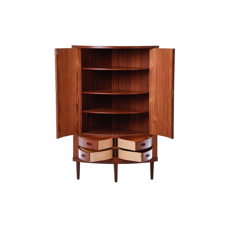 This unique bow front corner cabinet in teak provides extensive storage options with multiple swing-open drawers and adjustable interior shelves.