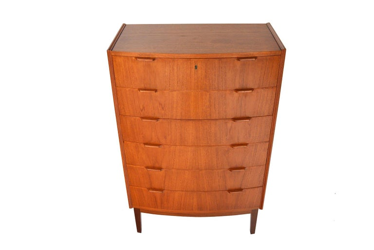 With a robust bow Front Design, this Danish modern teak highboy dresser offers simple lines and traditional form. Two carved pulls line each drawer front. In excellent original condition.