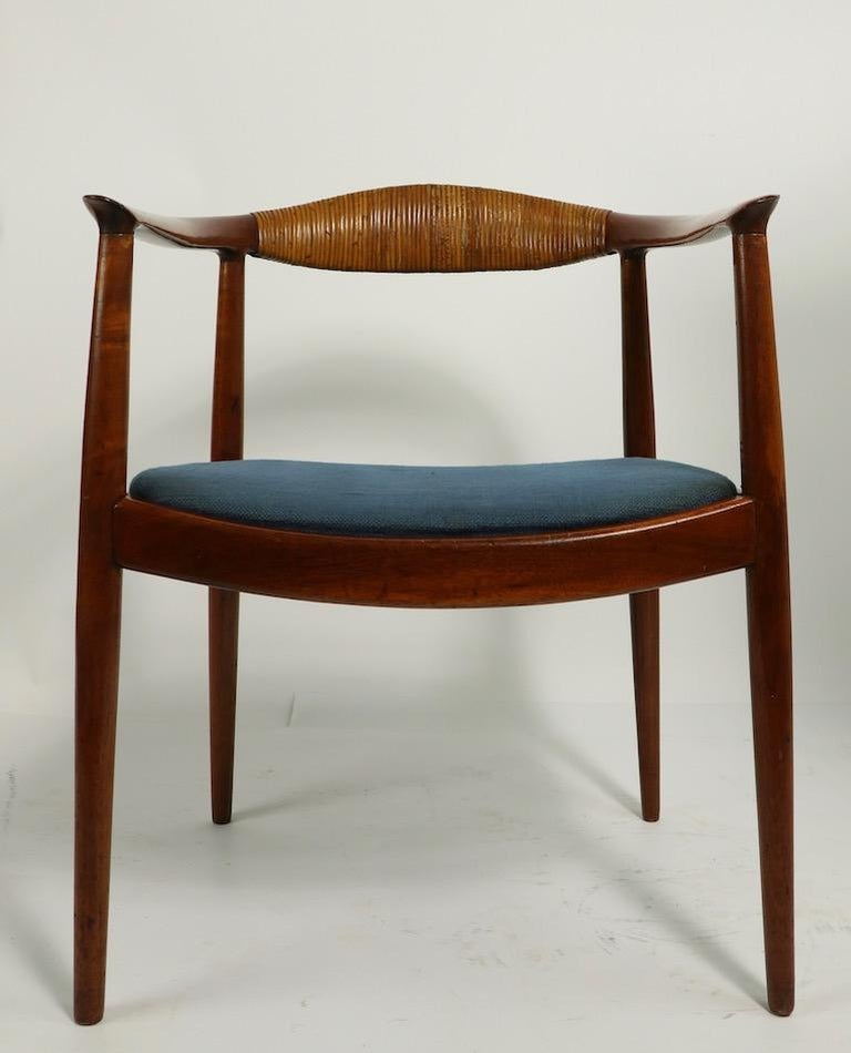 Sleek, sophisticated and architectural, wraparound armchair in solid rosewood, designed by Hans  Wegner  made by Johannes Hansen The chair has a solid rosewood frame, drop in upholstered seat, and wrapped cane backrest. The frame looks like it has a