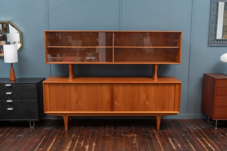 Danish modern teak credenza with matching removable hutch or display cabinet. High quality construction and design throughout with adjustable interior shelves and four slim drawers. Timeless and Classic Danish design, perfect for dining or for