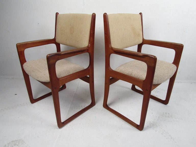 Stunning set of 12 Danish modern dining chairs by Benny Linden Design. Set includes two armchairs and ten chairs. Stylish design with sled legs, teak wood construction, and handsome joinery along the frames. These chairs are sure to be a great
