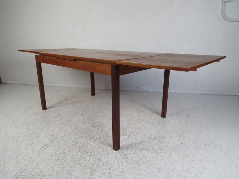 This stunning Mid-Century Modern dining table boasts a unique butcher block style wood grain on each of the leaves that complements the center. A convenient draw leaf design that expands from 53.25 inches wide all the way to 92.75 inches wide once