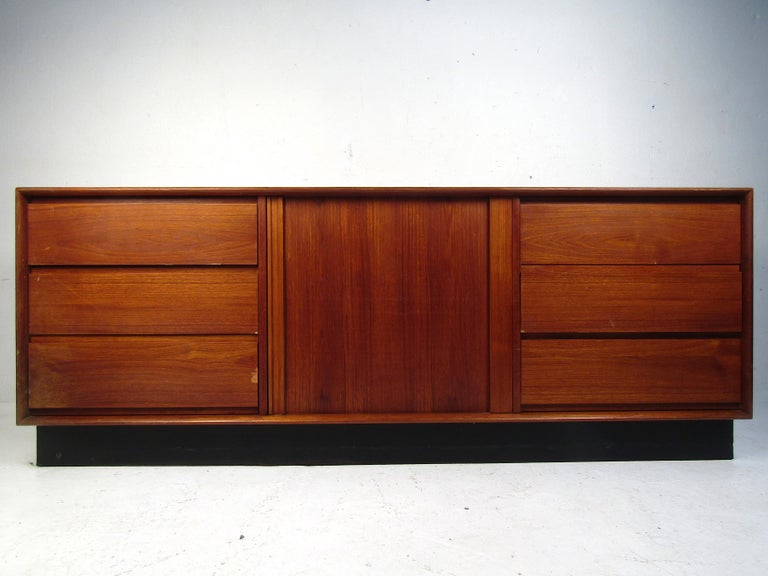 Stylish Danish Mid-Century Modern dresser by Art Furn. Good-looking teak veneer throughout, with six dovetail-jointed drawers on each flank of the case piece, complemented by cabinet space concealed by a tambour door in the center. Black skirt base.